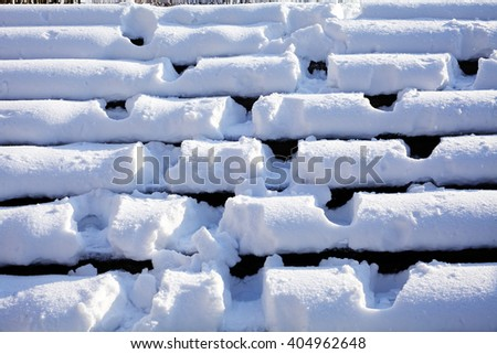 Lots of footprints on the stairs covered with snow - stock photo