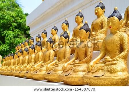 lots of golden Bhuddha images on pagoda base - stock photo