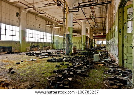 Lots of green mold on the floor of an abandoned factory.
