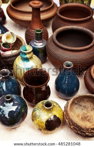 Lots of handmade earthenware - ceramic pots and vases at pottery shop. Colorful crockery background
