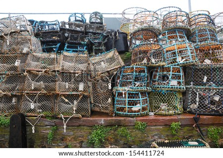Lots of lobster and crabbing pots piled up on the quayside - stock photo