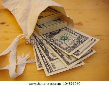 Lots of Money Flowing from a Canvas Money Bag - stock photo