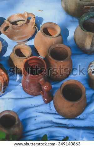 Lots of old handmade clay pots in a flea market