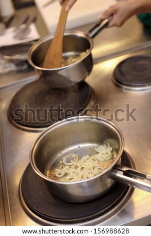 Lots of onion slices are put in a silver pan - stock photo