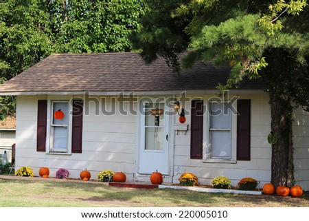 Lots of pumpkins and other decorations for fall season near a cozy house - stock photo