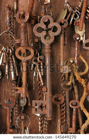 Lots of rusty keys hanging on nails in an old wooden key box.  - stock photo