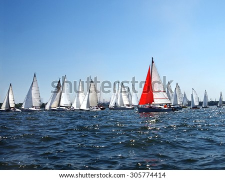 lots of sailboats on a blue surface of water against the blue sky - stock photo