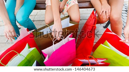 Lots of shopping bags and three girls in the city.