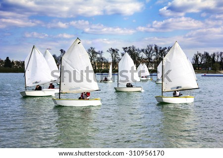 Lots of Small white boats sailing on the lake  - stock photo