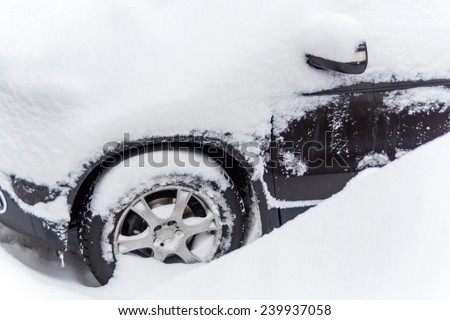 lots of snow on a parked car in the winter. - stock photo