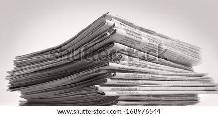 lots of stacked newspapers in light back - stock photo