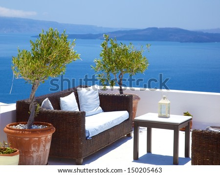 lots of stylish plant pots with a sofa overlooking the Aegean sea