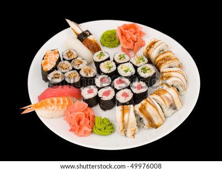 lots of sushi rolls on a big dish, isolated on black, clipping path - stock photo