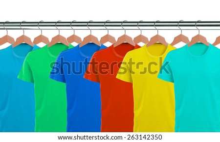 Lots of T-shirts on hangers isolated on white background - stock photo