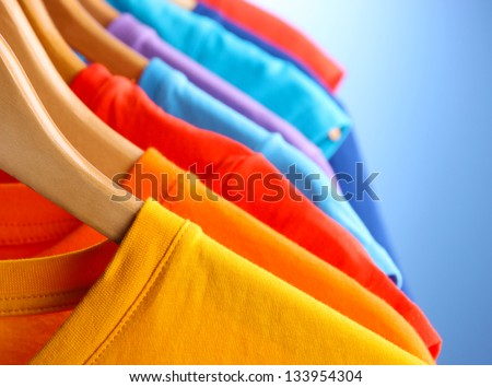 Lots of T-shirts on hangers on blue background - stock photo