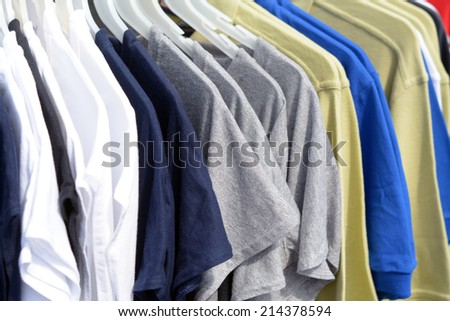 Lots of T-shirts on hangers on the outdoor store  - stock photo