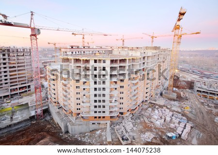 Lots of tower cranes build large residential building at evening. - stock photo