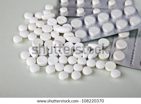 Lots of white pills in their containers - stock photo
