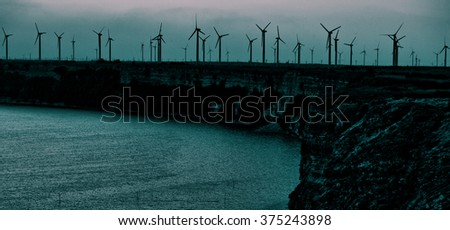 Lots of wind turbine, electricity generators installed on a sea or ocean cliff, tinted horizontal image.