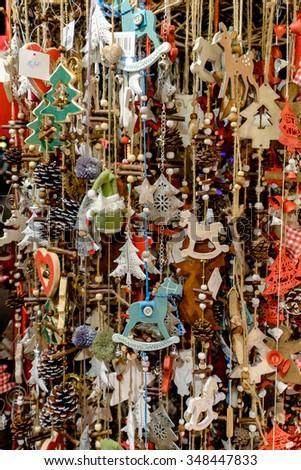 Lots of wooden Christmas ornaments hanging on ropes at a market in Vienna, Austria.