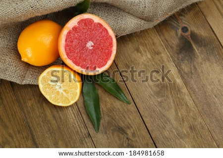 Lots ripe citrus on wooden background - stock photo
