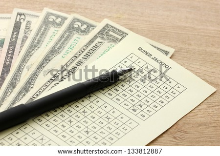 Lottery ticket with pen and money, on wooden background