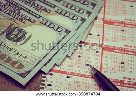 Lotto ticker with pen and one hundred dollar bills