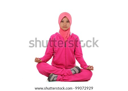 Lotus position - Portrait of a cute young mslim female practicing yoga isolated on white