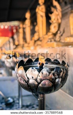 Lotus shaped oil cup lamp with burning candle in Thailand temple - stock photo