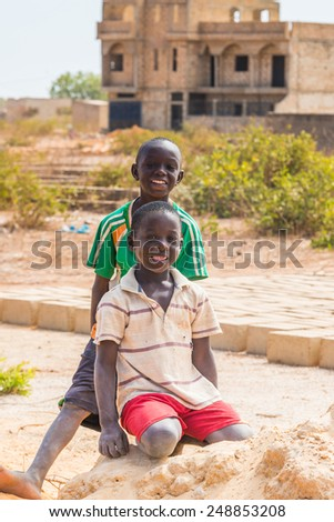 LOUGA, SENEGAL - MAR 15, 2013: Unidentified Senegalese boys play over the sand and smile Children in Senegal suffer of poverty due to the unstable economic situation - stock photo