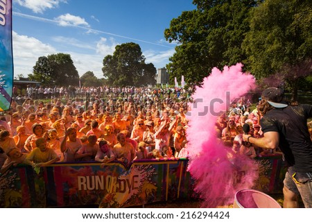 LOUGH CUTRA, GORT, IRELAND - SEPTEMBER 6: Unidentified people having fun get showered in powdered dye during annual RUN OR DYE, the 5K event, on September 6, 2014 in Lough Cutra, Gort, Ireland. - stock photo