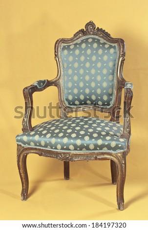 Louis XV armchair on yellow ocher background - stock photo