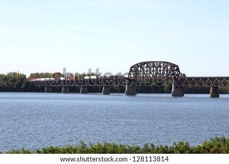 LOUISVILLE, KY - NOVEMBER 10: A CSX train crosses over a steel railroad truss drawbridge over the Ohio River, on November 10, 2012 in Louisville, Kentucky. This bridge was built in 1868. - stock photo