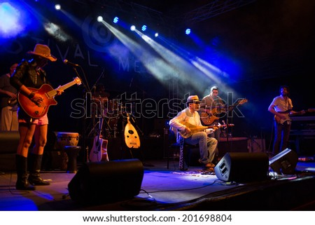 LOULE - JUNE 27: Moroccan instrumentalist and singer Nour Eddine performs on stage at festival med, a world music festival, in Loule, Portugal, June 27, 2014  - stock photo