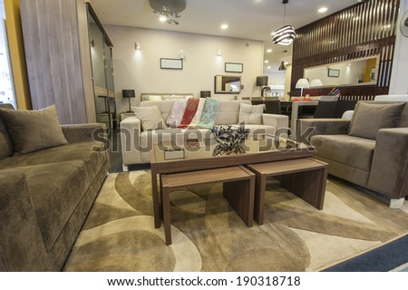 Lounge area of furniture show room with sofa and glass table