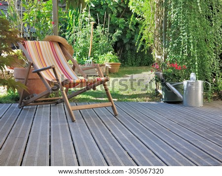 lounge chair on wooden terrace garden - stock photo