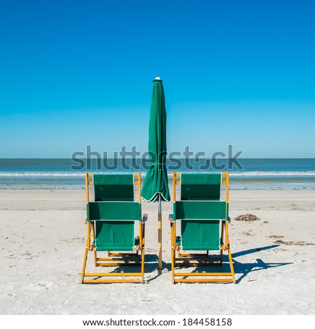Lounge chairs along popular Fort Myers Beach on the west coast of Florida. - stock photo