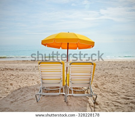 Lounge chairs and colorful umbrellas at the beach in Miami FLorida - stock photo