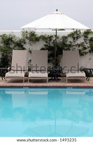 lounge chairs by the pool #3 - stock photo