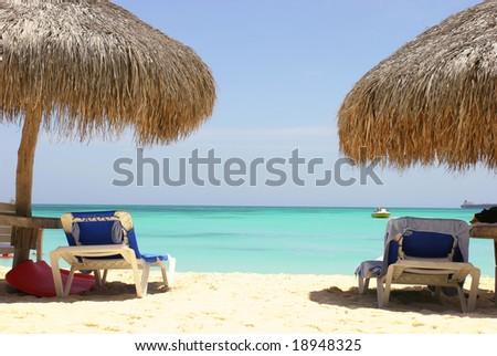 Lounge chairs on caribbean sea - stock photo