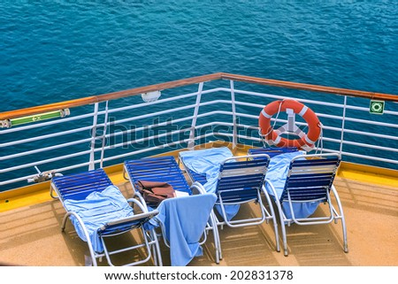 lounge chairs on deck of cruise ship in sunny caribbean - stock photo