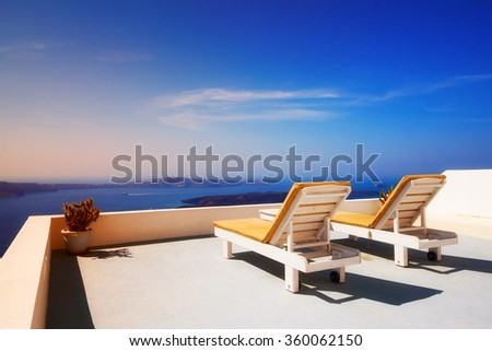 Lounge chairs overlooking the Santorini caldera, Imerovigli village, Greece - stock photo