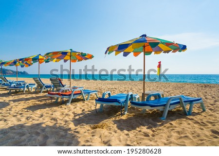 Lounge chairs with sun umbrellas on a beach