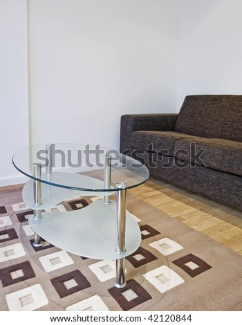 lounge detail with modern sofa and glass top coffee table