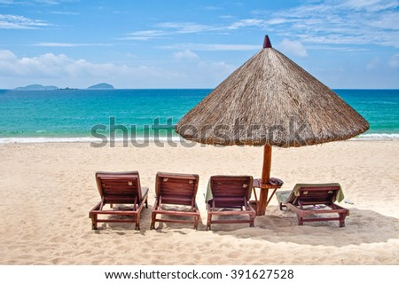 Loungers and straw umbrella on a tropical beach - stock photo