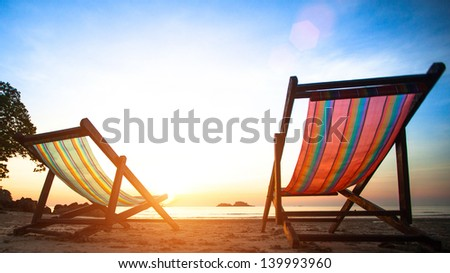 Loungers on the deserted coast sea at sunrise - stock photo