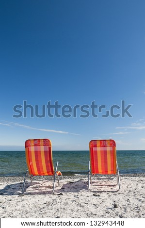 Lounging beach chairs on the Lake Ontario shoreline with large copy space area in the deep blue sky
