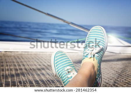lounging on a catamaran sailboat trampoline . calm blue ocean and cloudless blue sky are in the background.