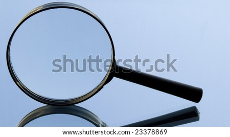 Loupe and blue reflection on a mirror. Search and education concept with magnifying glass. - stock photo