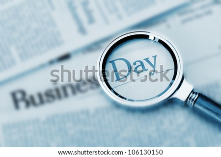 Loupe lies on the newspaper with title Business day. A photo close up. Selective focus - stock photo
